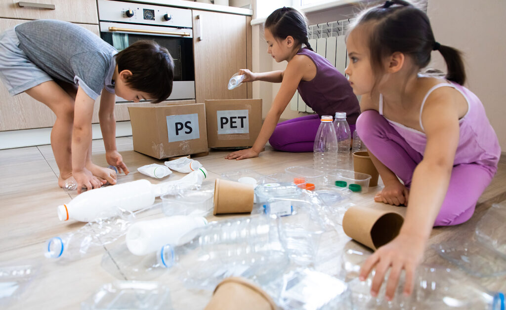 Three young children sorting recyclable plastic into various containers.