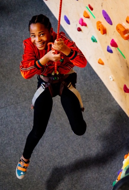 A young black girl hanging from a rock climbing harness. She's smiling up at the camera.
