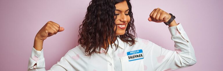 """A woman wearing a nametag that says """"Hello I am Dreamer"""" and flexing her muscles."""