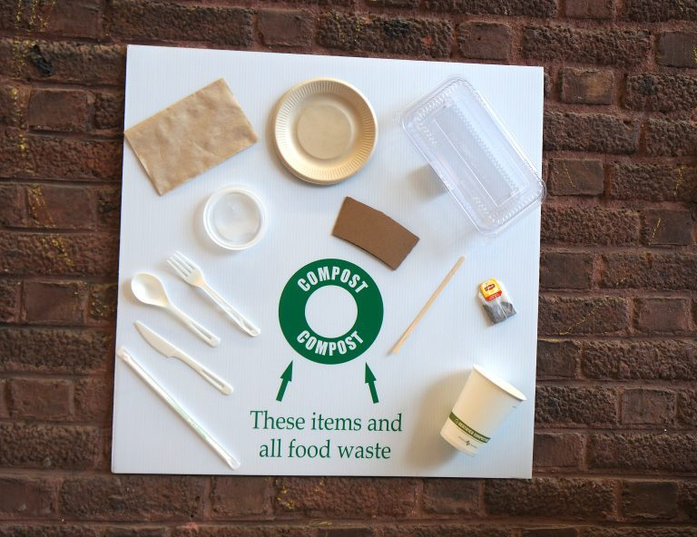 A sign with single-use utensils glued to it as an example of what items can be composted.