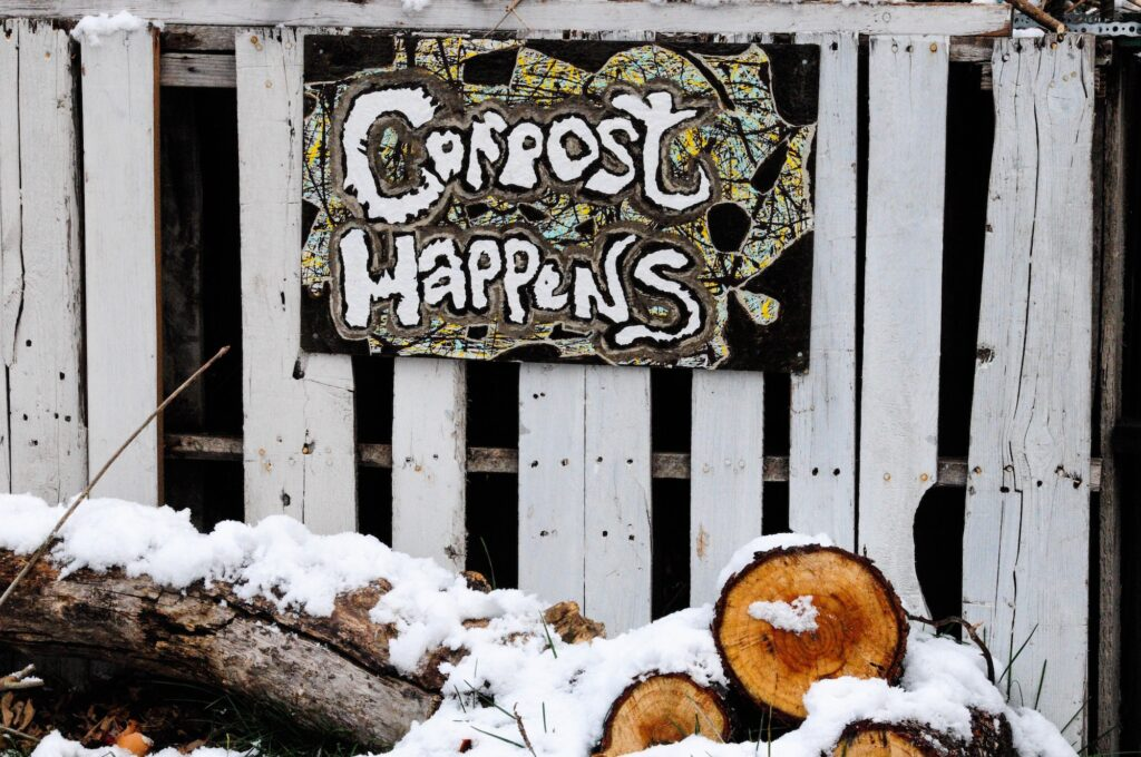 """A hand-painted sign that says """"Compost Happens"""" nailed to a fence. There is snow on the ground."""
